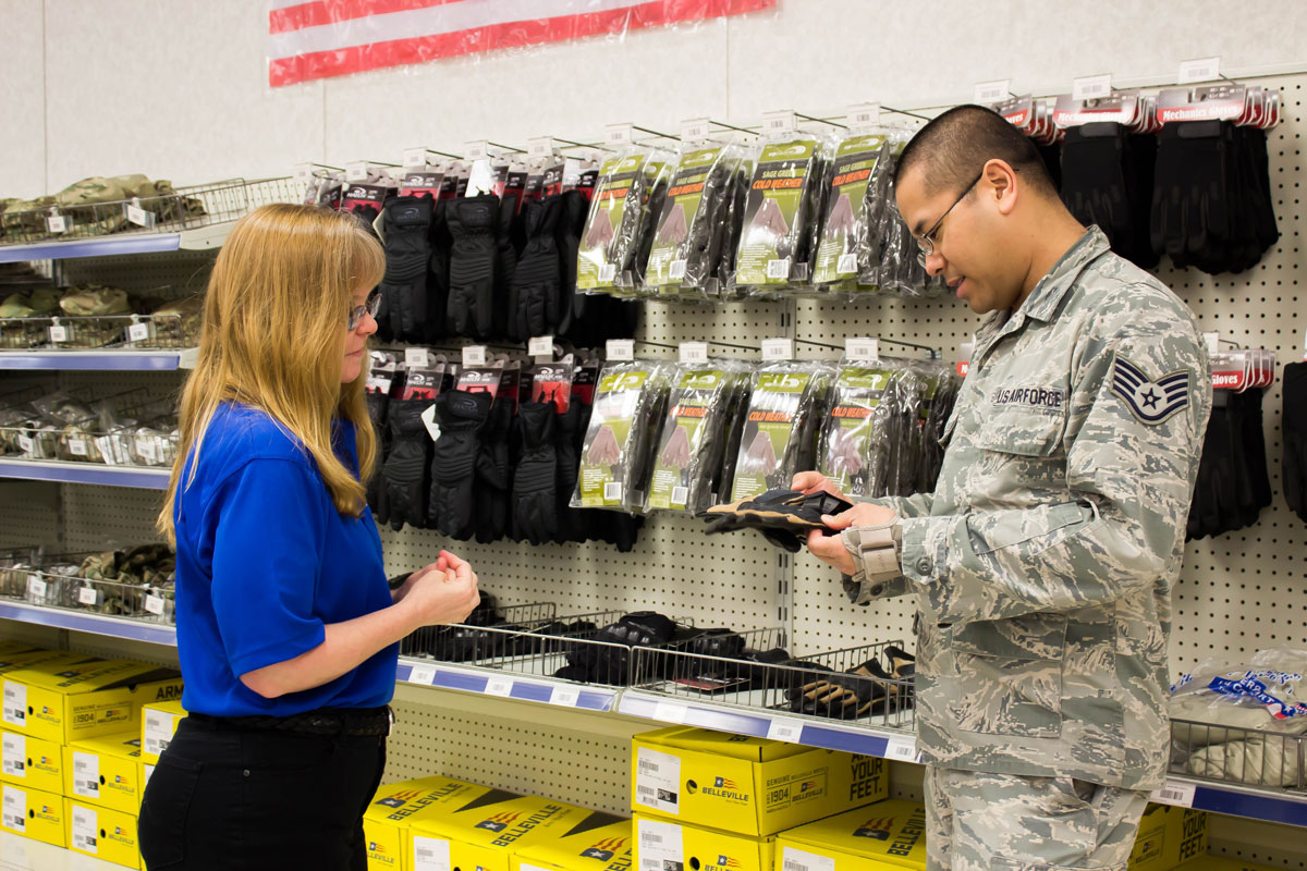 Kim Utley assisting soldier purchasing gloves